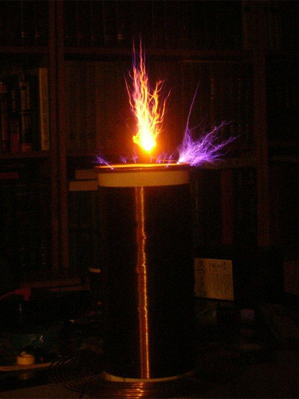 Трансформатор Тесла в работе, темнота, соль на терминале (даёт оранжевое свечение)