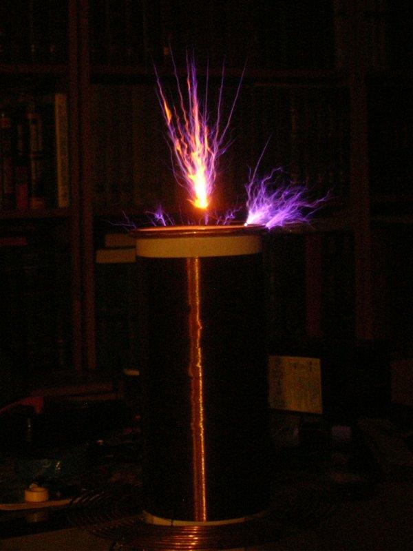 Трансформатор Тесла в работе, темнота, соль на терминале иссушивается (но ещё даёт оранжевое свечение)